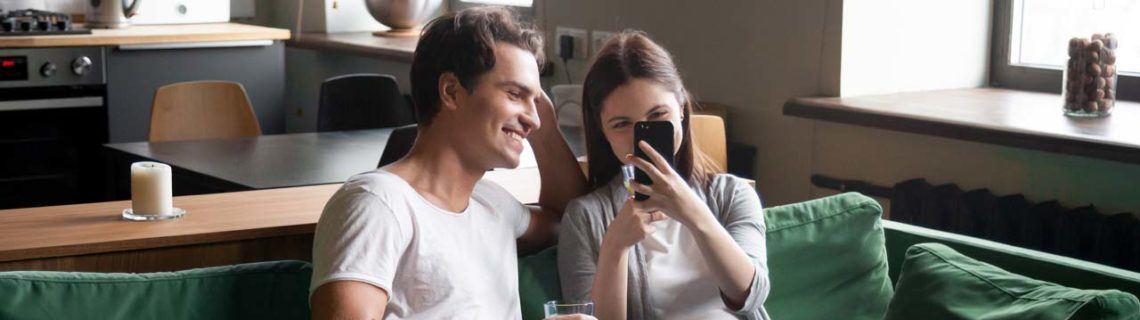 För kvinnor antikonception ett par som sitter på soffan smartphone