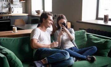 Para mujeres anticoncepción pareja sentada en el sofá teléfono móvil