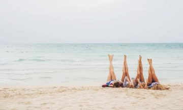 Women on beach with legs up in the air