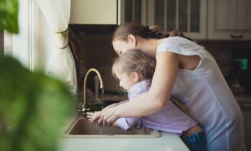Mother daughter washing hands