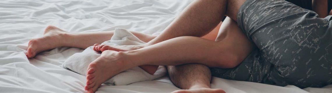 ETS sífilis pareja haciéndose caricias en la cama