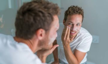 Skin care acne man looking in mirror